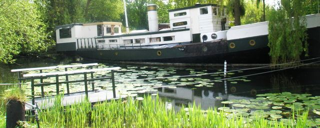 picture of a houseboat on Chichester Canal near its mouth into Chchester Harbour at Birdham Pool, West Sussex